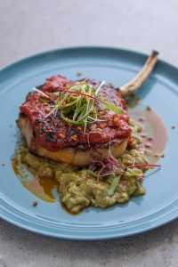 Tomahawk pork chop with Bagoong glaze - A thick-cut of pork loin grilled, and glazed with our signature tomato-bagoong jam, and served over roasted eggplant mash